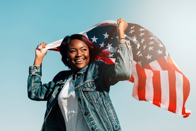 Black smiling female raising hands with usa flag