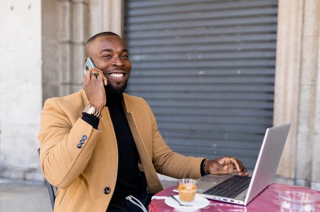 Черный улыбающийся человек разговаривает по телефону, сидя в кафе с помощью портативного компьютера.