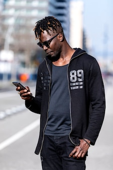 Черный улыбающийся человек в солнечных очках с помощью мобильного телефона на открытом воздухе