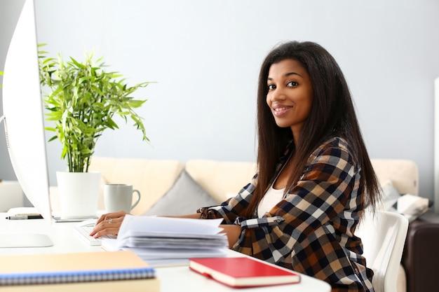 Черная улыбающаяся женщина сидит на рабочем месте, работая с настольным пк