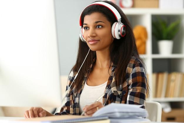 Black smiling woman sitting at workplace wearing headphones