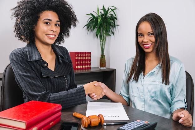 Черные улыбающиеся женщины пожимают друг другу руки за столом с оборудованием