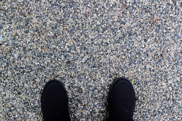 Black sneakers on colorful gravel on the floor in the park