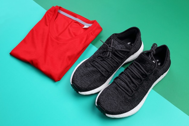 Black sneakers and folded red running t-shirt