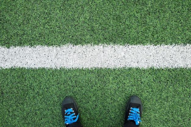 스포츠 게임과 비즈니스에서 성공을 의미하는 흰색 선이 있는 축구장이나 축구장에 있는 검은색 운동화