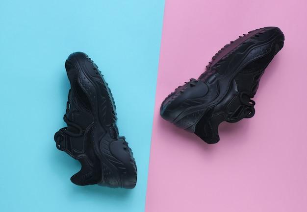 Black sneakers on pastel table. top view, minimalism