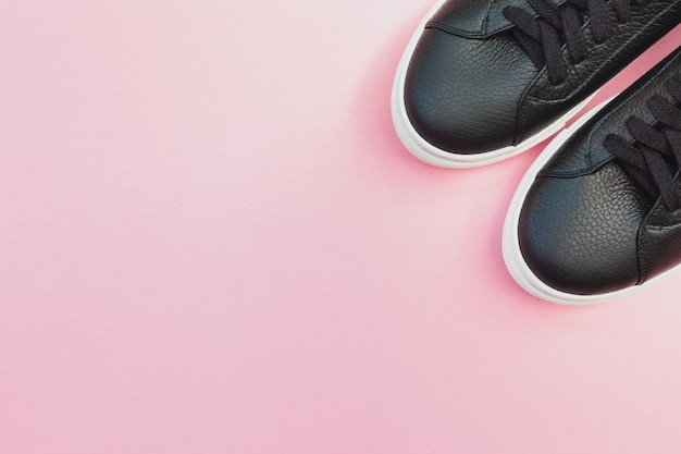 Black sneakers on pink background. copy space