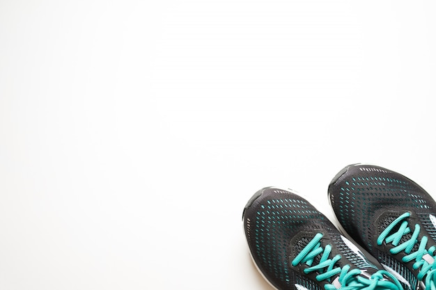 Black sneakers for run with green elements and green laces on a white background.