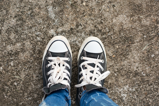 Black sneakers shoes on road concrete