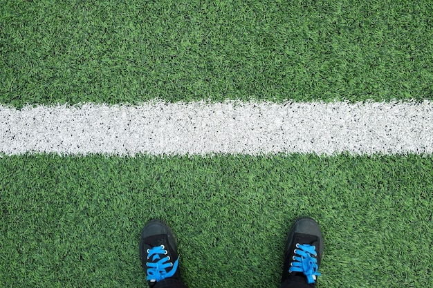 Black sneakers on soccor or football field with the white line meaning to succussful in sport game and business