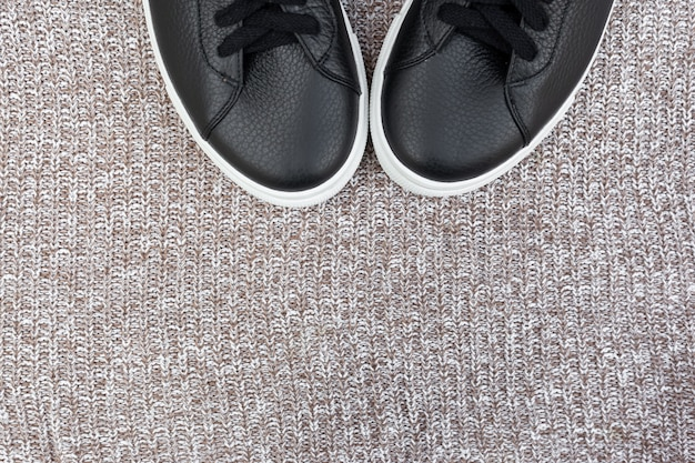 Black sneakers on woolen background. flat lay, top view. fashion blog concept. copy space for text