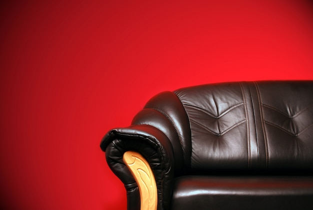 Black sofa in front of a red wall