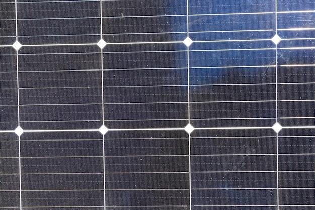 Черные солнечные панели, освещенные солнечным светом, батареи с песком и грязью на поверхности