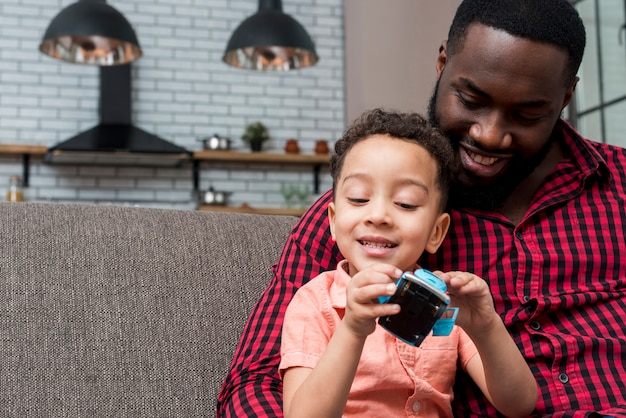 Black son and father sitting with toy car
