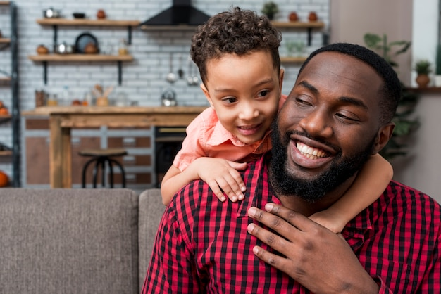 Black son hugging father from behind