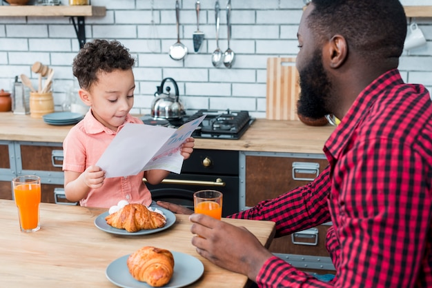 Black son reading greeting card while having breakfast with father