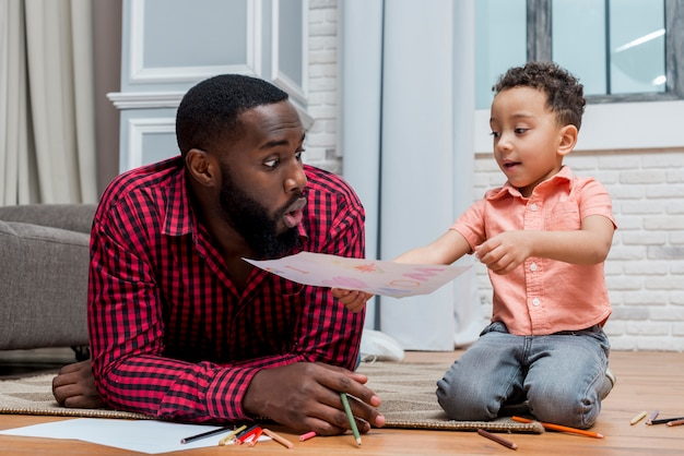 Black son showing drawing to amazed father