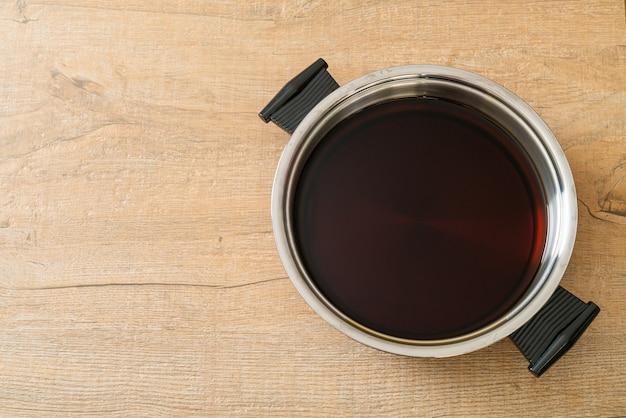 샤브샤브나 스키야키를 위한 냄비에 담긴 검은 수프 - 일본 음식 스타일