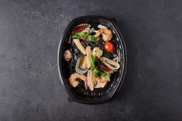 Черные спагетти неро с морепродуктами, помидорами и базиликом в черном пластиковом контейнере на темном фоне