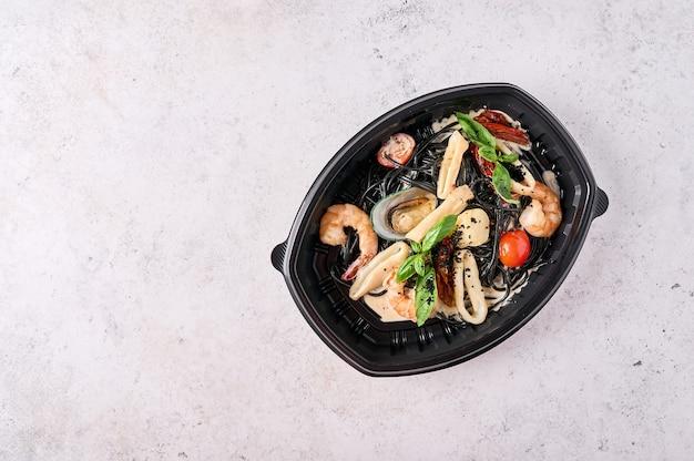 Черные спагетти неро с морепродуктами, помидорами и базиликом в черном пластиковом контейнере на светлом фоне