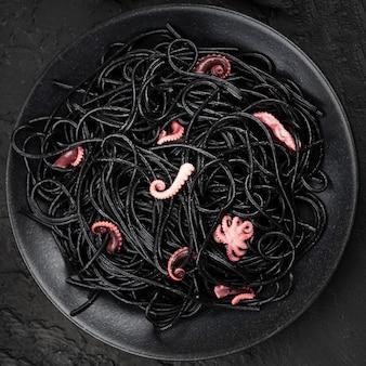 Черные спагетти на тарелке с кальмарами