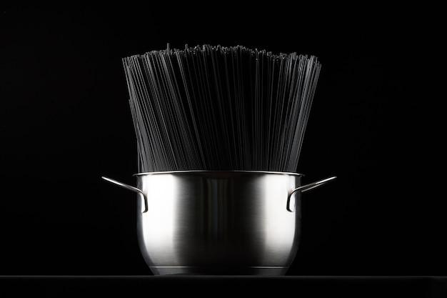 Черные макароны спагетти в кастрюле на черном