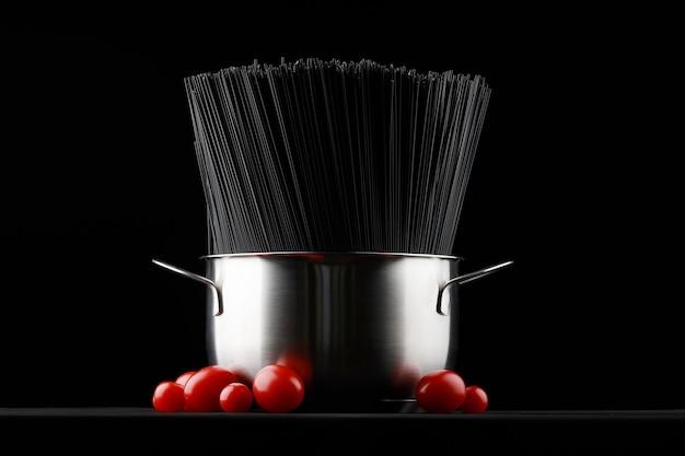 Черные макароны спагетти в кастрюле со свежими помидорами на черном