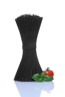 バーゼルの葉と白い壁に赤いトマトの黒いスパゲッティ。