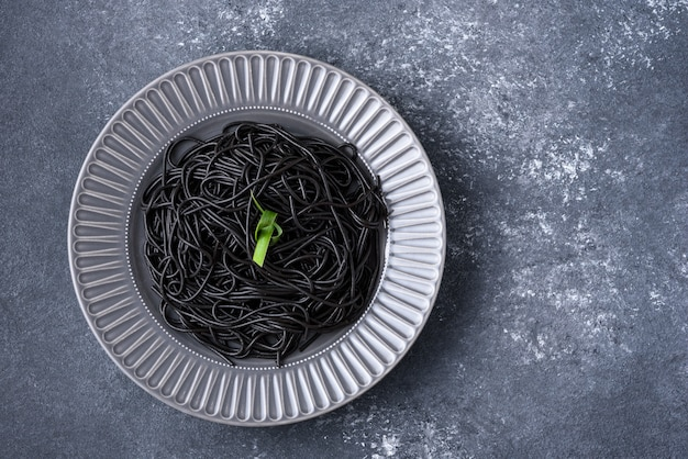 Black spaghetti with ink cuttlefish with green leaf on gray plate on gray background with copy space, black pasta concept
