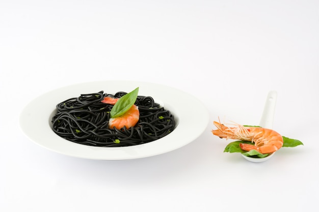 Black spaghetti with prawns and basil isolated on white