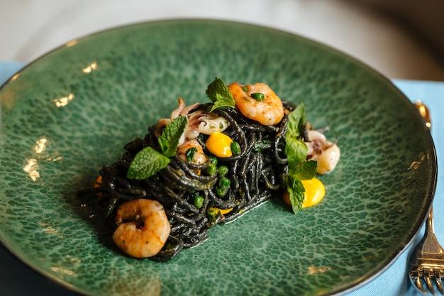 青いテーブルにシーフードとサフランソースが入った黒いスパゲッティ