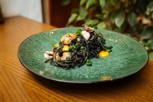 Черные спагетти с морепродуктами и шафрановым соусом на деревянном столе