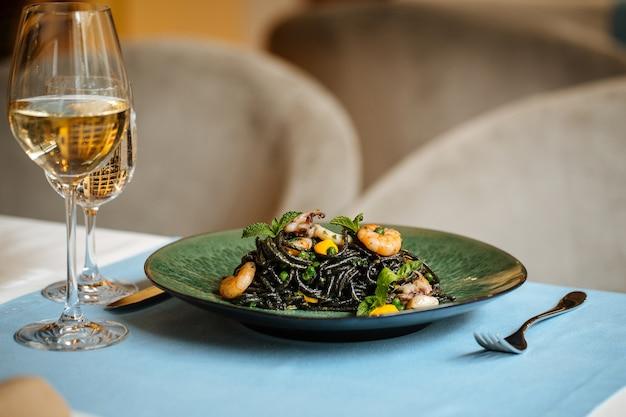 青いテーブルの上にシーフードとサフランソースと白ワインの黒いスパゲッティ