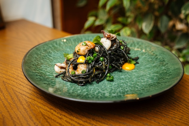 Black spaghetti with seafood and saffron sauce on the wooden table