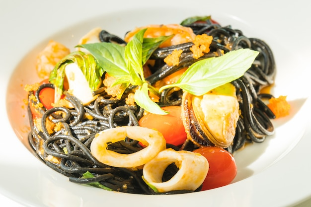 Black spaghetti with seafood in white plate
