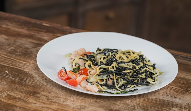 Black spaghetti with spicy mixed seafood on white plate