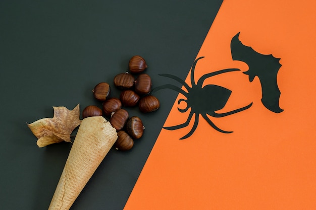 Черный паук, летучая мышь и вафельный рожок мороженого с каштанами на черно-оранжевой бумаге