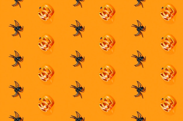 Black spiders and halloween pumpkins laid in lines