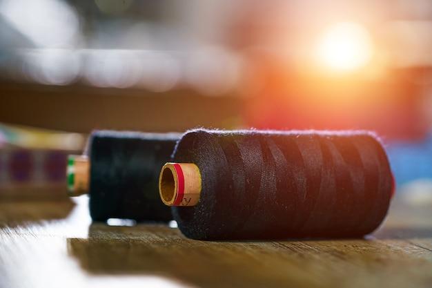 Черные катушки на деревянном столе. концепция портного. концепция шитья.