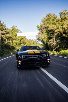A black sport car with two yellow stripes driving on the road.
