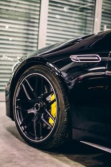 Black sport model car in front of the garage