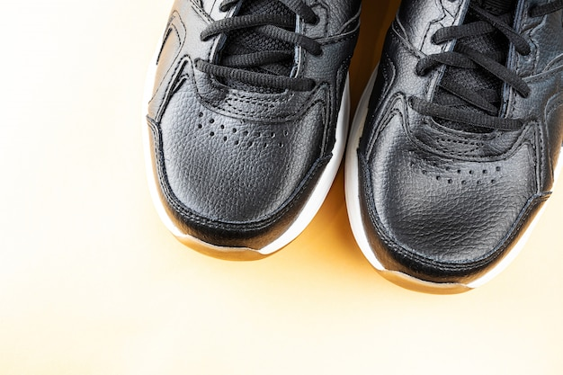 Black sports leather sneakers close up. comfortable casual shoes concept. light space, copy space.