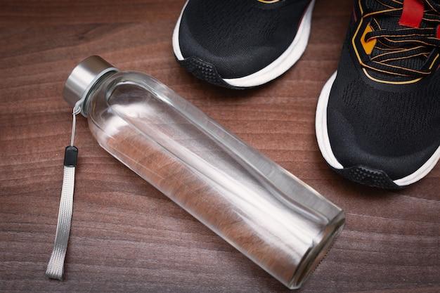 黒のスポーツシューズと水のボトル