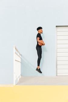 黒のスポーツマンがポーチでバスケットボールでジャンプ