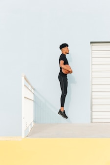 Black sportsman jumping with basketball at porch