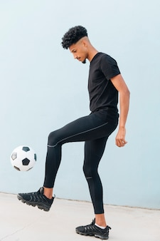 Black sportsman kicking football at blue wall background