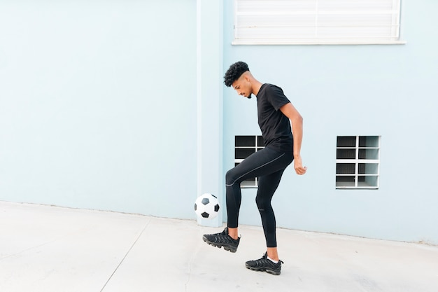 Black sportsman kicking football at porch