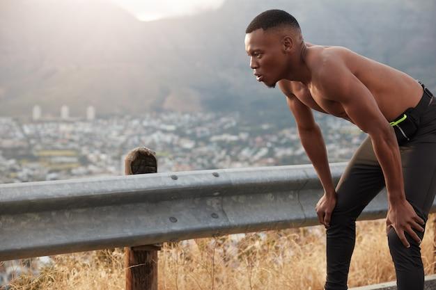 흑인 운동가는 무릎을 꿇고 워밍업 운동과 야외 운동, 스포츠 목표, 검은 색 스포츠 바지를 입고,