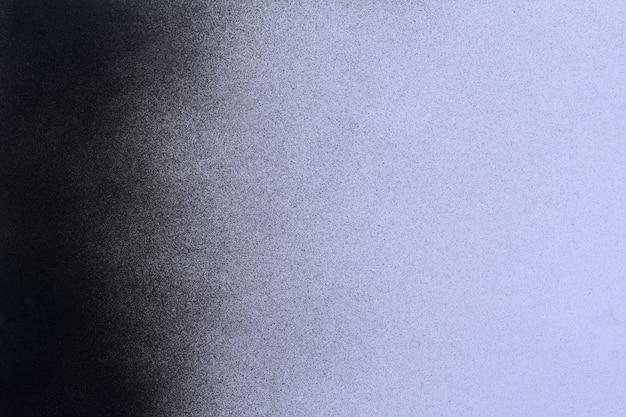 ライラック色の紙の背景に黒のスプレーペイント