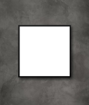 Black square picture frame hanging on a dark concrete wall.